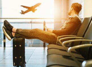 man-with-phone-watching-plane-take-off-be07fe36